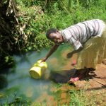 The Water Project: Shirugu Community, Jeremiah Mashele Spring -  Nancy Shakava Fetching Water At The Spring