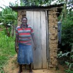 The Water Project: Shirugu Community, Shapaya Mavonga Spring -  A Community Member Stands Beside Her Latrine