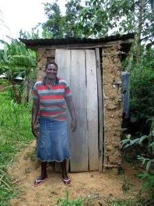 The Water Project:  A Community Member Stands Beside Her Latrine