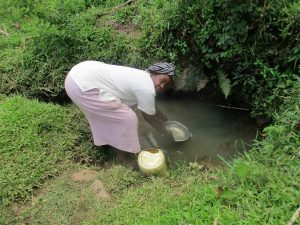 The Water Project:  Filling Up Pot To Fill Up Jerrycan With Spring Water