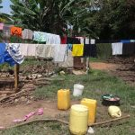 The Water Project: Ematetie Community, Weku Spring -  Water Containers And Cloths Drying On A Clothline