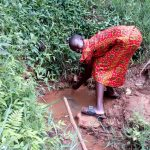 The Water Project: Asimuli Community, John Omusembi Spring -  Girl Washes Her Hands In The Spring