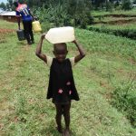 The Water Project: Chepnonochi Community, Chepnonochi Spring -  Child Carrying Water On Her Head