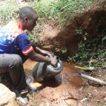 The Water Project: Chepnonochi Community -  Collecting Water From Spring