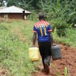 The Water Project: Chepnonochi Community -  Duncun Carrying Water To His Home