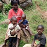 The Water Project: Chepnonochi Community, Chepnonochi Spring -  Mary Amboka With Her Kids Use Water From Chepnonochi Spring