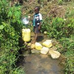 The Water Project: Masera Community, Murumba Spring -  Child Fills Large Jerrycan