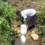 The Water Project: Masera Community, Murumba Spring -  Fetching Water By Scooping