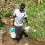 The Water Project: Masera Community, Murumba Spring -  Woman Carries Recently Fetched Water From Spring