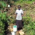 The Water Project: Masera Community, Murumba Spring -  Woman Stands With Bucket To Collect Water