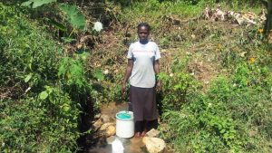 The Water Project:  Woman Stands With Bucket To Collect Water