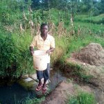 The Water Project: Elutali Community, Obati Spring -  Holding Up Bucket Of Collected Stagnant Water