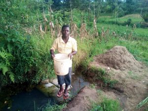 The Water Project:  Holding Up Bucket Of Collected Stagnant Water
