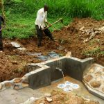 The Water Project: Ivulugulu Community -  Filling In The Spring Box
