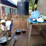 The Water Project: Namalasire Primary School -  Cook Washing Utensils With Tank Water