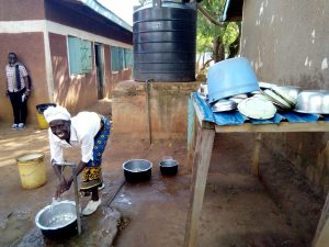 The Water Project:  Cook Washing Utensils With Tank Water