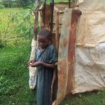The Water Project: Emulakha Community, Alukoye Spring -  Child Stands Outside Of Latrine