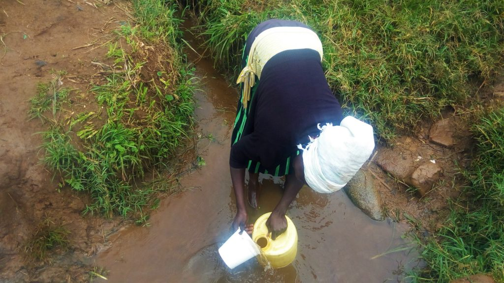 The Water Project : kenya18117-woman-fills-container-with-water-at-source