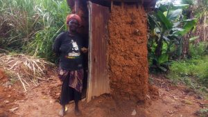 The Water Project:  Woman Stands Next To Latrine