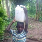 The Water Project: Nambatsa Community -  Young Boy Carrying Home Water From The Unprotected Hole