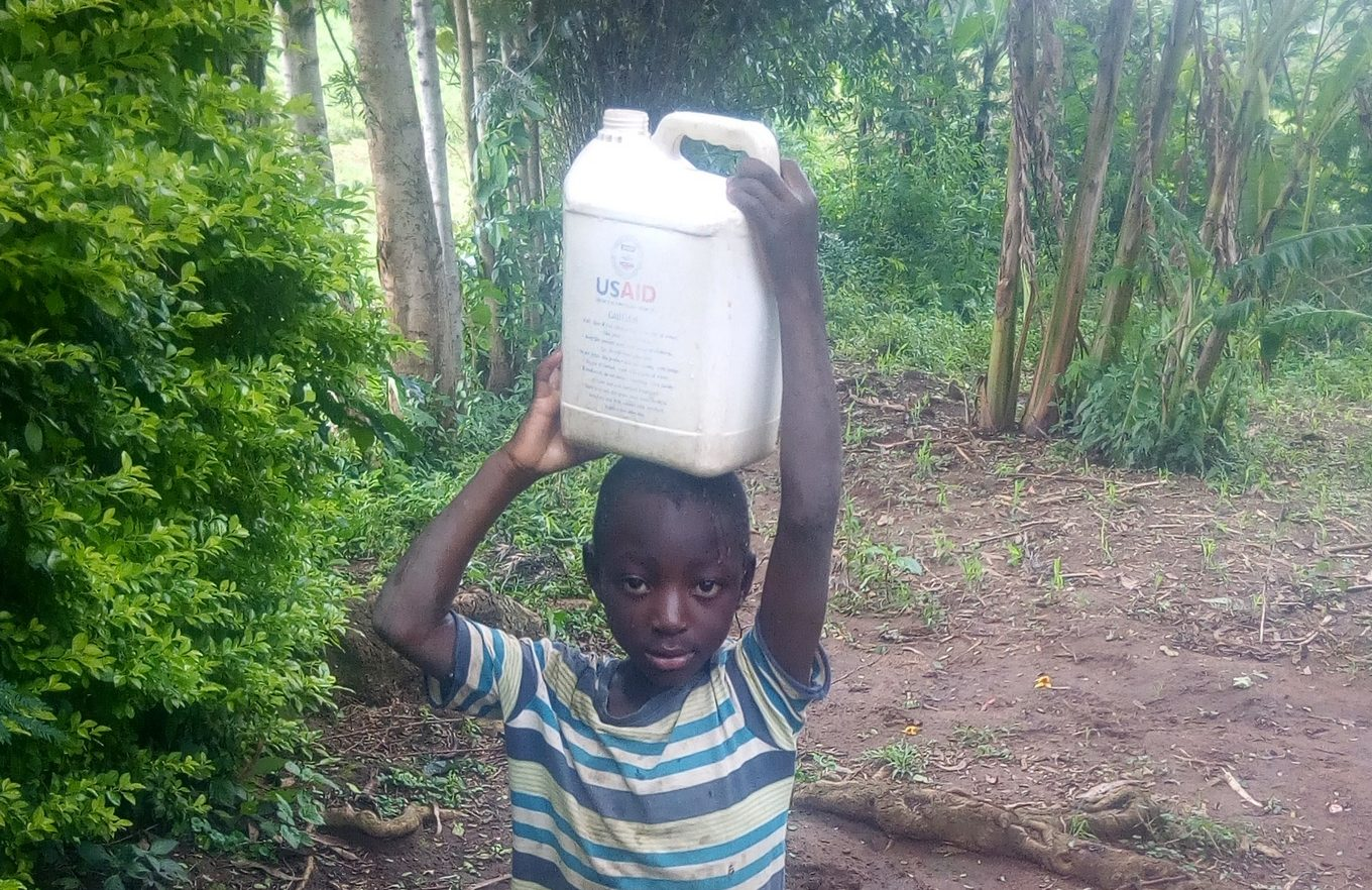 The Water Project : kenya18119-young-boy-carrying-home-water-from-the-unprotected-hole