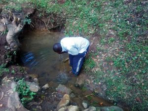 The Water Project:  A Community Member Drinks Water Directly At The Spring