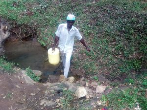 The Water Project:  Man Carries Jerrycan Filled With Water Away From Spring
