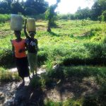 The Water Project: Mukhangu Community, Okumu Spring -  Community Members Carrying Water From The Spring