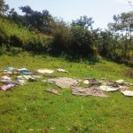 The Water Project: Mukhangu Community, Okumu Spring -  Drying Cloths On The Ground