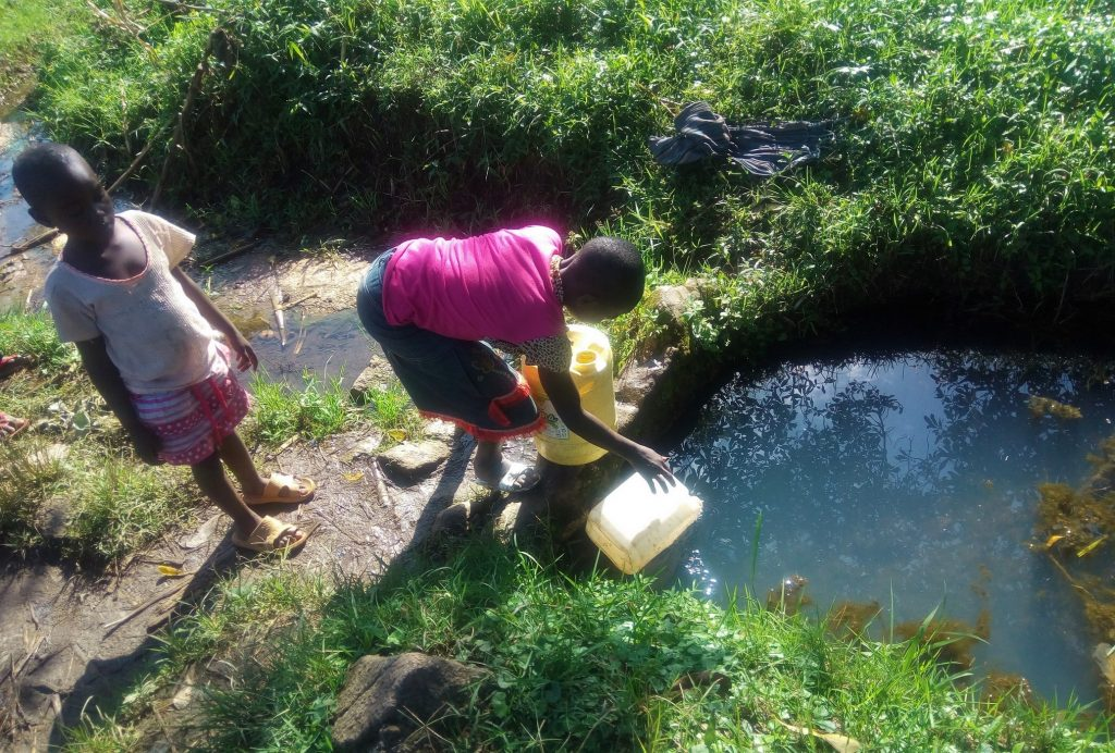 The Water Project : kenya18129-filling-smaller-container-with-water-at-spring