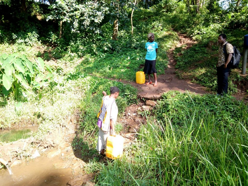 The Water Project : kenya18130-woman-walking-out-of-spring-with-filled-jerrycan