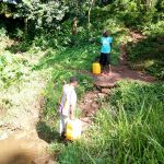 The Water Project: Irumbi Community, Okang'a Spring -  Woman Walking Out Of Spring With Filled Jerrycan