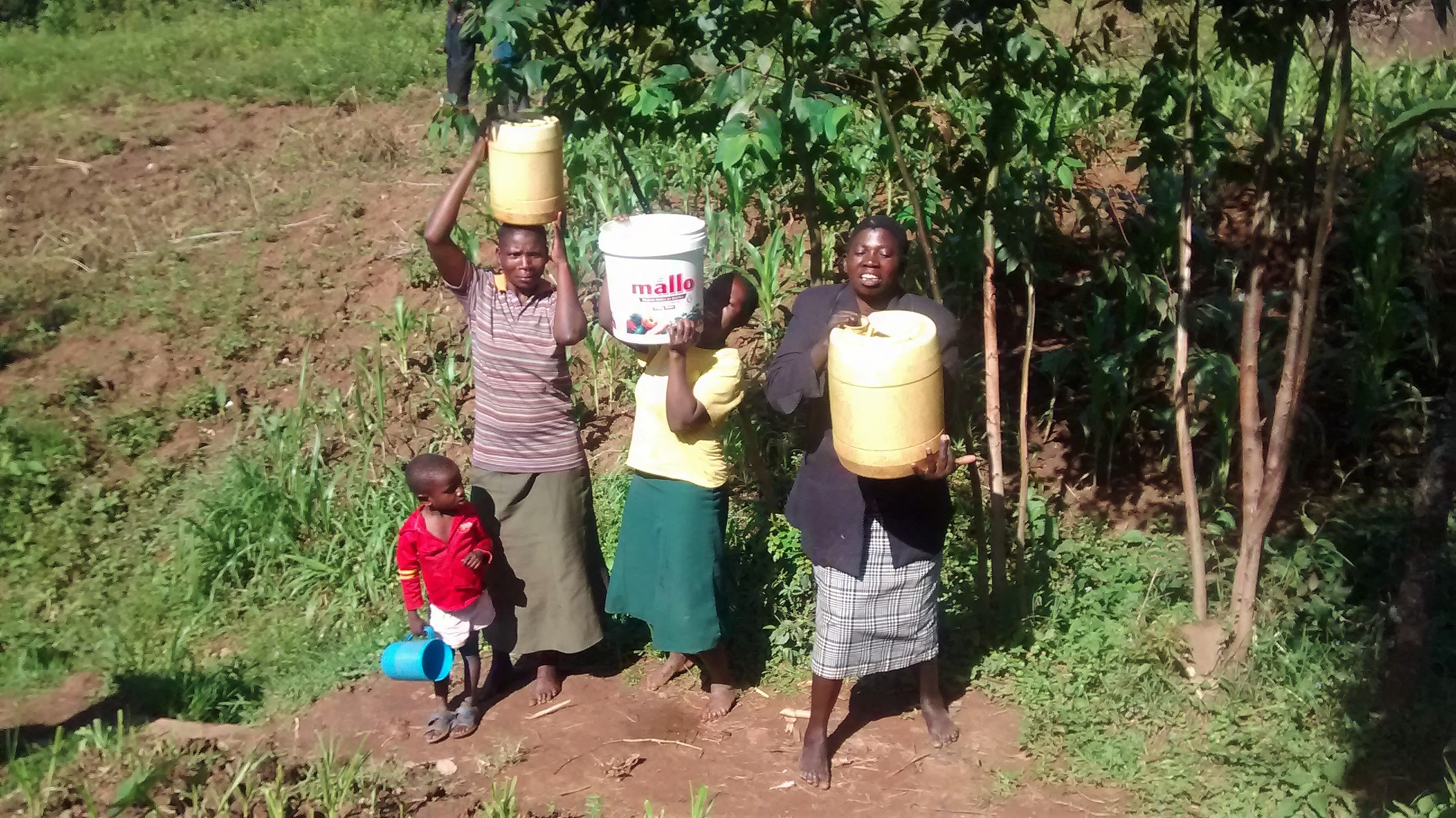 The Water Project : kenya18133-lifting-jerrycans-filled-with-water-onto-heads
