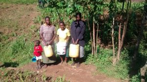 The Water Project:  Women And Girls Stand With Water Containers