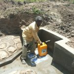 The Water Project: Futsi Fuvili Community, Simeon Shimaka Spring -  Collecting Water From Protected Spring
