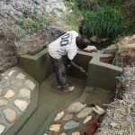 The Water Project: Futsi Fuvili Community, Simeon Shimaka Spring -  Paving Cement Walls