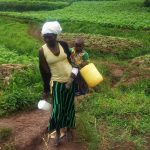 The Water Project: Emulakha Community -  Mary Indiangala Carrying Her Water Container And Her Child Heading To The Unprotected Water Source