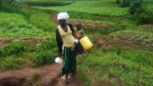 The Water Project:  Mary Indiangala Carrying Her Water Container And Her Child Heading To The Unprotected Water Source