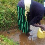 The Water Project: Emulakha Community -  Mary Scoops Water At Their Unprotected Spring