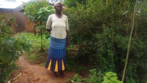 The Water Project:  Mrs Caroli Poses Beside The Hole In The Ground That Acts As Her Latrine