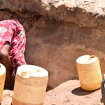 The Water Project: Utuneni Community A -  Getting Scoop Hole Water