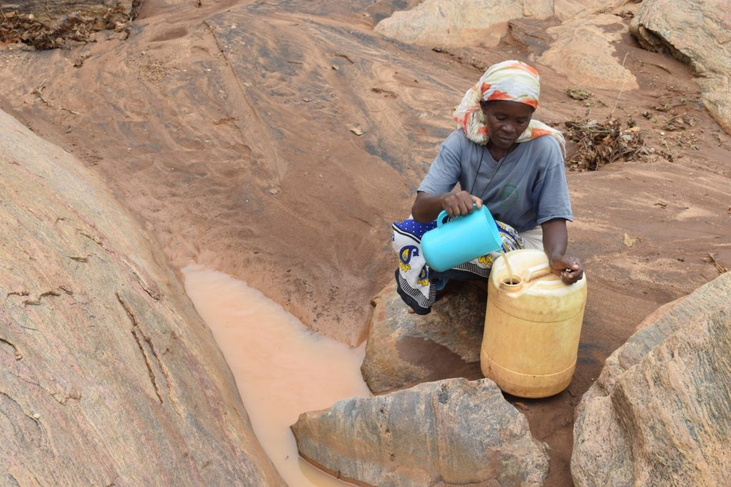 The Water Project : kenya18189-pouring-water-into-jerrican
