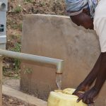 The Water Project: Ngaa Community B -  Filling Water At First Well