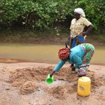The Water Project: Kaliani Community -  Collecting Water From Scoop Hole