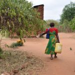 The Water Project: Ndiani Primary School -  Carrying Water To Kitchen