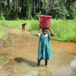 The Water Project: DEC Mathen Primary School -  Girl Carrying Water