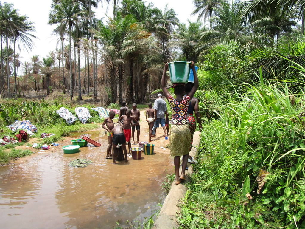 The Water Project : sierraleone18272-people-bathe-wash-clothes-and-gather-water-at-open-source