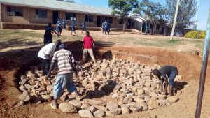 The Water Project:  Laying Rocks For Tank Foundation