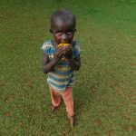 The Water Project: Emwanya Community -  A Child Enjoying A Fruit At The Training