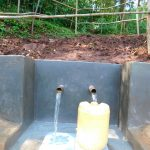 The Water Project: Emwanya Community, Josam Kutsuru Spring -  Clean Water Flows Into Jerrican